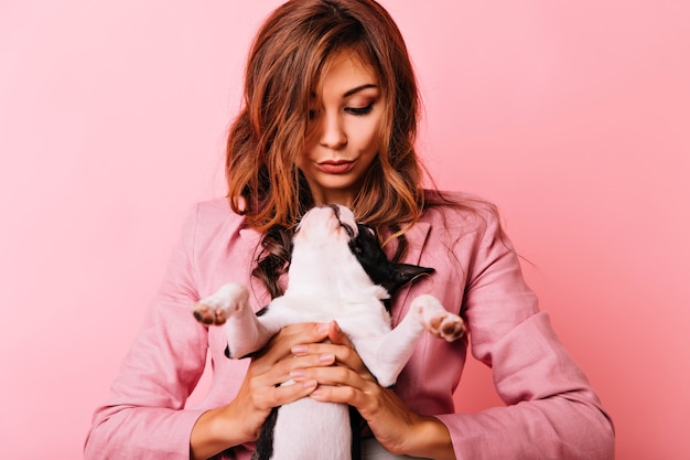 Bouledogue français mignon regardant la femme au gingembre. plan intérieur d'une femme frisée enthousiaste tenant son chiot.