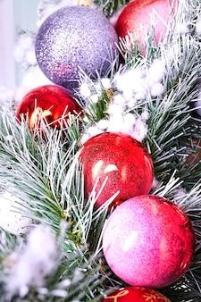 Boules sur un arbre de noël artificiel. boules colorées ou orbes sur les branches d'épinette couvertes de neige