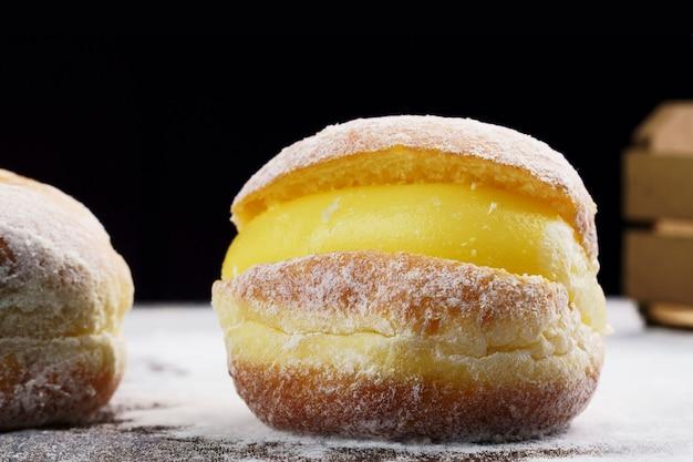 Boules de berlin, connues sous le nom de sonho au brésil sur une table en bois avec du sucre glace éparpillé. il se compose d'une pâte sucrée frite remplie d'une crème et de sucre sur le dessus. mise au point sélective.