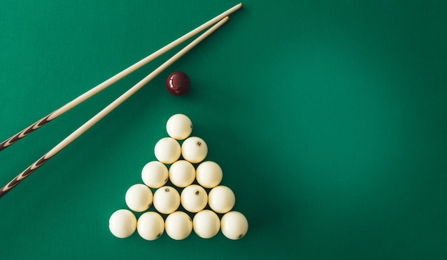 Boules de billard russes, queue, triangle, craie sur une table.