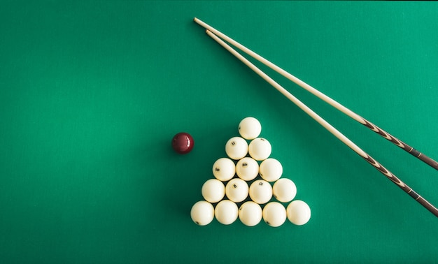 Boules de billard russes, queue, triangle, craie sur une table.