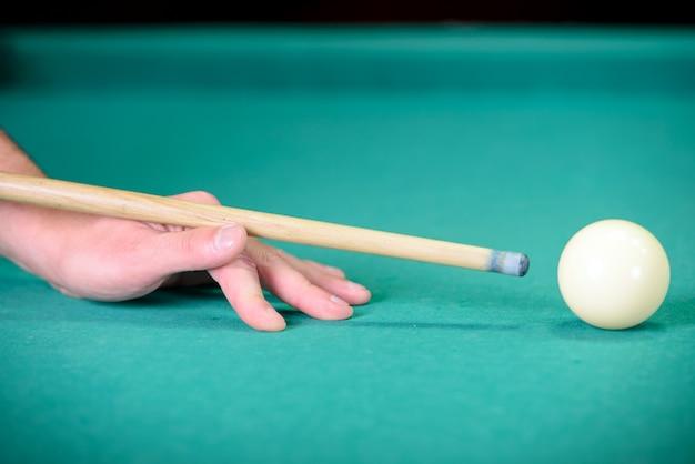 Boules de billard sur la table verte et boule blanche au premier plan.