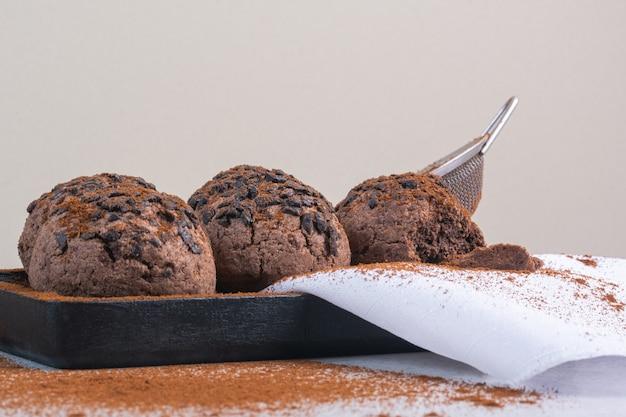 Boules de biscuits aux pépites de chocolat sur une serviette sur une assiette en bois, sur le marbre.