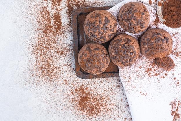 Boules de biscuits aux pépites de chocolat sur une serviette sur une planche, sur le marbre.