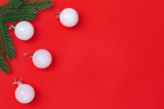 Boules blanches de noël et brindilles de sapin sur papier rouge