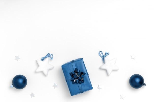Boules bleues, étoiles blanches, coffret cadeau sur une surface blanche