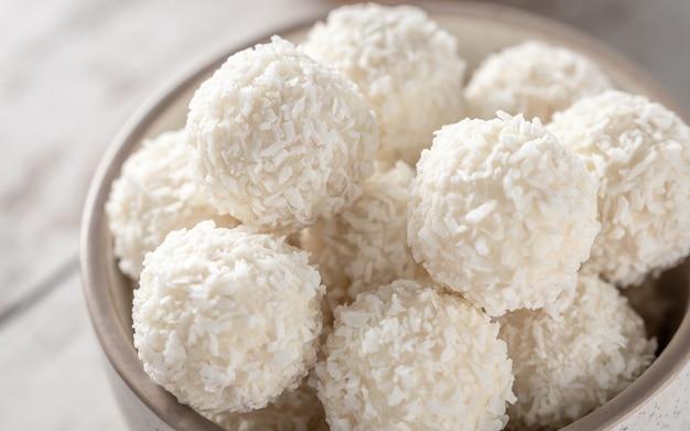 Boules de bonbons au chocolat blanc et à la noix de coco dans le bol de près, mise au point sélective