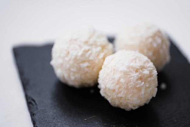 Boules de bonbons de noix de coco blanche dans des plats de schiste plaque sur fond en bois rustique.