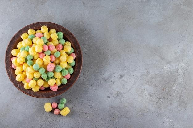 Boules de céréales colorées placées sur une assiette brune.