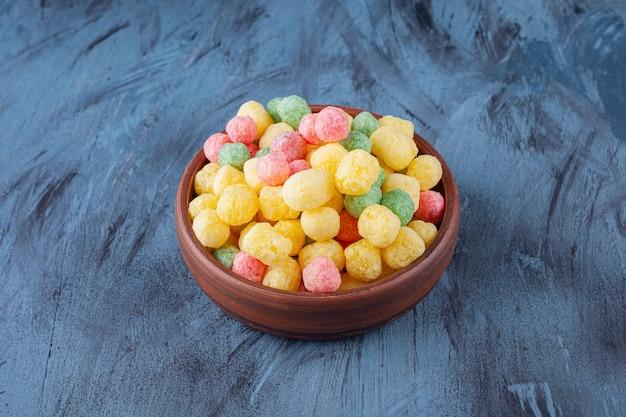 Boules de céréales colorées placées dans un bol en bois.