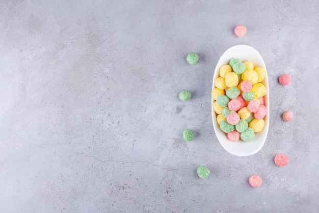 Boules de céréales colorées placées dans un tableau blanc.