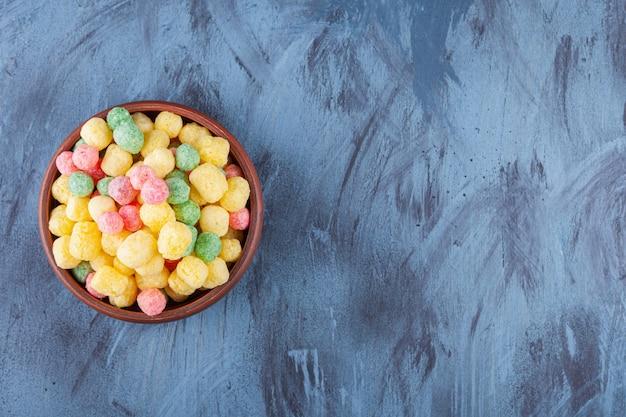 Boules de céréales colorées placées sur un fond coloré.
