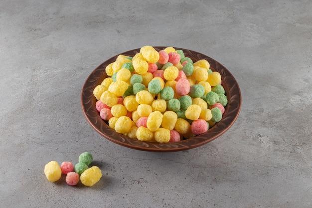 Boules de céréales saines colorées placées dans un bol en céramique.