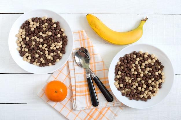 Boules de chocolat et de lait dans un bol et des fruits sur une surface en bois blanche. petit déjeuner sain aux céréales. petit déjeuner bébé. bébé mange. régime équilibré.