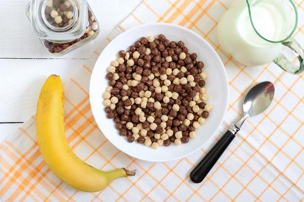 Boules de chocolat et de lait entiers, fruits et lait sur une surface en bois blanche. petit déjeuner sain aux céréales. petit déjeuner bébé. bébé mange. régime équilibré
