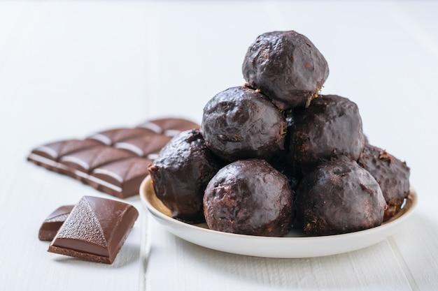 Boules de chocolat trempées de noix râpées et de fruits secs dans un bol sur une table en bois blanc. délicieux bonbons faits maison.