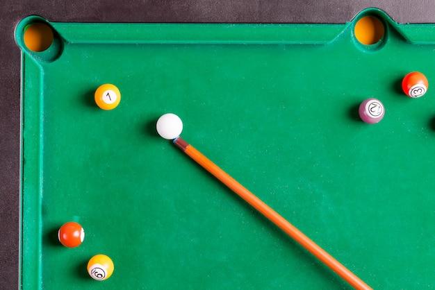 Boules colorées de billard avec queue en bois sur table verte. snooker, jeu de billard. vue de dessus.