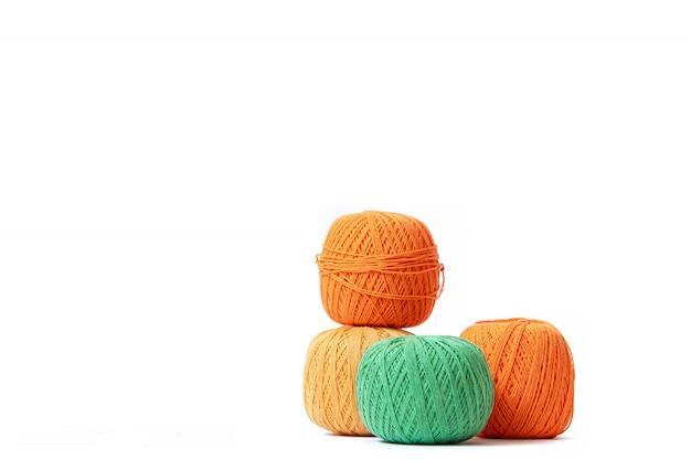 Boules colorées de fil à crocheter sur fond blanc. copiez l'espace. les enchevêtrements sont disposés en colonne. article sur le crochet. sélection de fils pour le crochet.