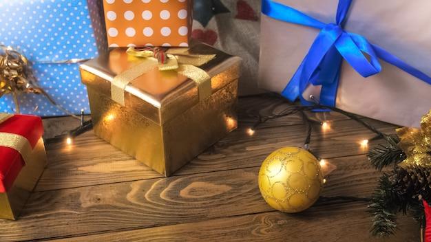Boules colorées, guirlandes et cadeaux de noël sur un bureau en bois