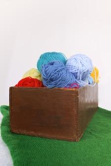 Boules colorées lumineuses de fil et aiguilles à tricoter dans une boîte en bois sur fond blanc avec tapis tricoté vert.