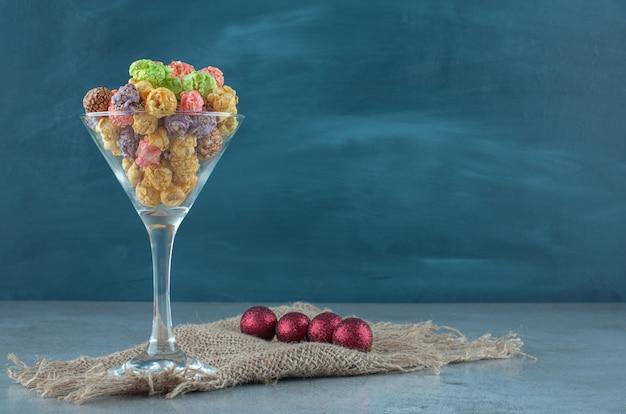 Boules à côté d'un support en verre avec du maïs soufflé confit sur une surface en marbre