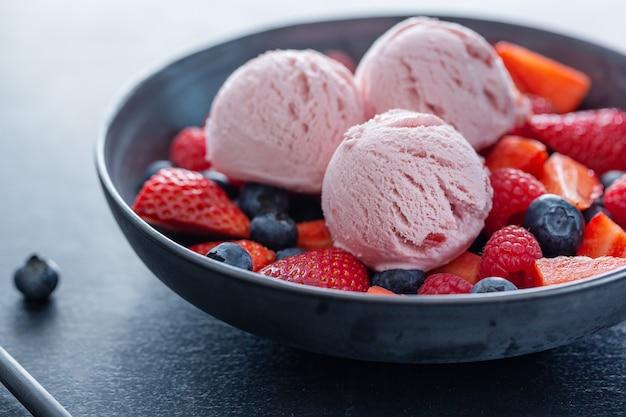 Boules de crème glacée aux fraises fruitées servies sur assiette avec des fruits. fermer