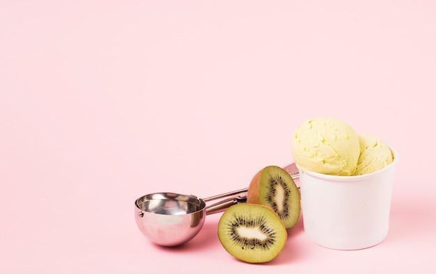 Boules de crème glacée dans une tasse près de kiwi et scoop