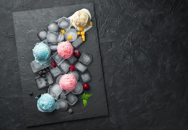 Boules de crème glacée de différents types sur la glace sur un mur noir