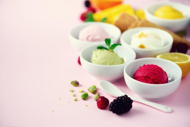 Boules de crème glacée rouges, violettes, jaunes, vertes dans des bols, cornets de gaufres, baies, orange, mangue, citron, menthe, pistache