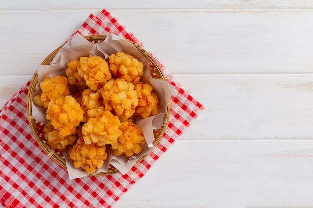 Boules de crevettes couvertes de panées frites sur la surface en bois blanc.