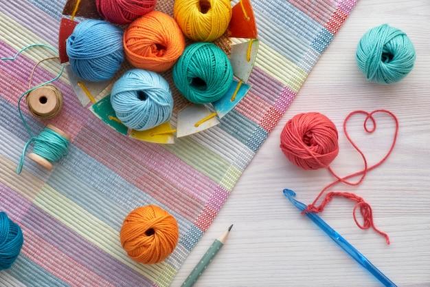 Boules de crochet et de laine, vue de dessus sur bois clair