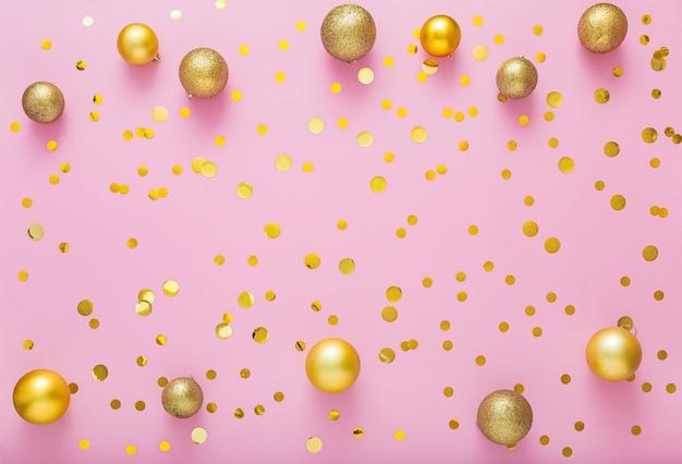 Boules de décoration festive or de noël, confettis sur rose.