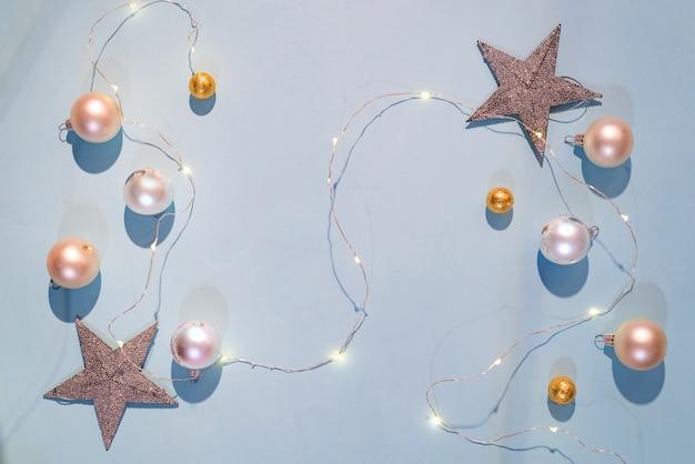 Boules de décorations de noël mates et blanches brillantes, guirlande de noël sur fond bleu