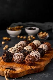 Boules énergétiques de noix, flocons d'avoine et fruits secs sur fond sombre