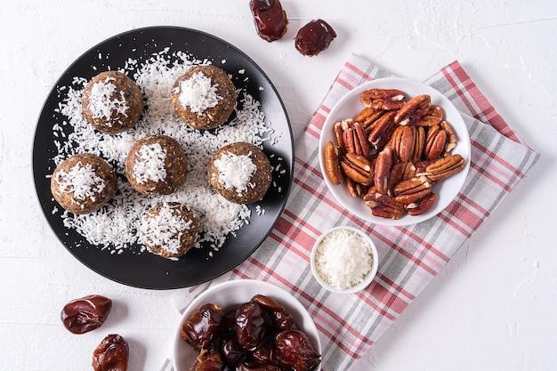 Boules énergétiques saines et biologiques à base de dattes, pruneaux, raisins secs, cacahuètes, copeaux de noix de coco, en plaque noire sur blanc
