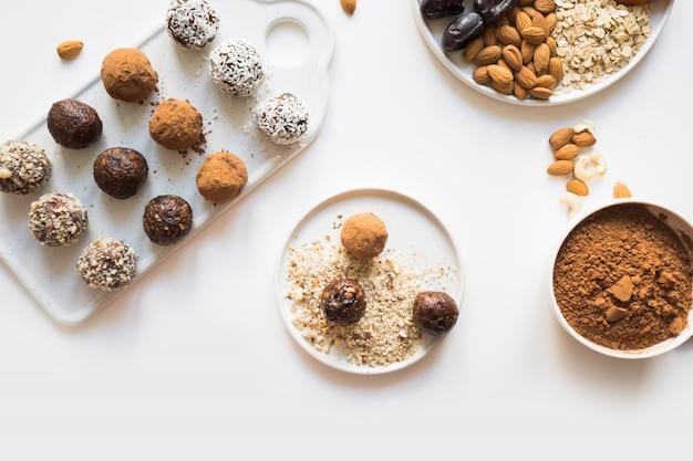 Boules d'énergie au cacao et noix sur blanc.