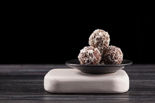 Boules d'énergie avec des bonbons à la noix de coco bonne nutrition maison sur fond sombre