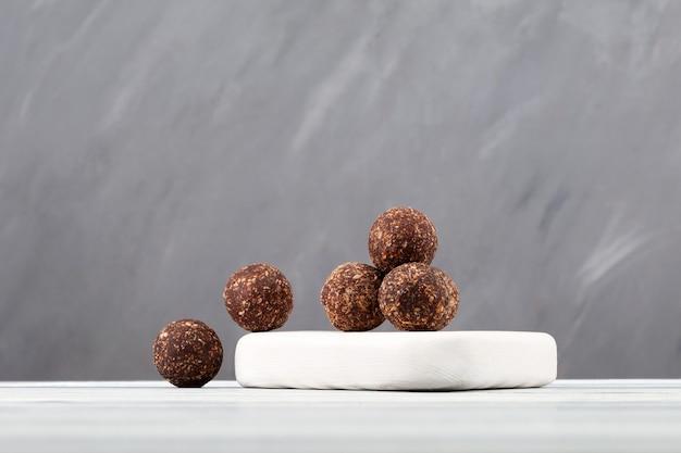 Boules d'énergie de bonbons végétaliens crus avec poudre de noix de coco et de caroube