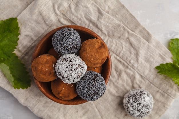Boules d'énergie brute maison végétalien sain avec caroube, pavot et noix de coco dans un bol en bois, vue de dessus. concept de nourriture végétalienne saine.