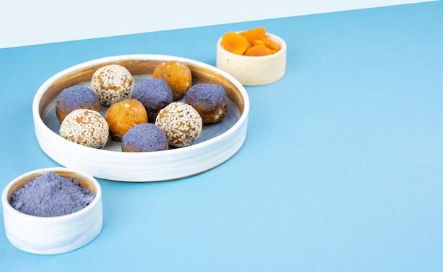 Boules d'énergie faites maison de poudre de thé de pois de papillon bleu matcha dans un bol en céramique sur une vue de dessus