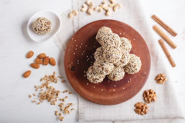 Boules d'énergie gâteaux aux amandes, sésame, noix de cajou, noix, dattes et blé germé, vue de dessus, espace copie.