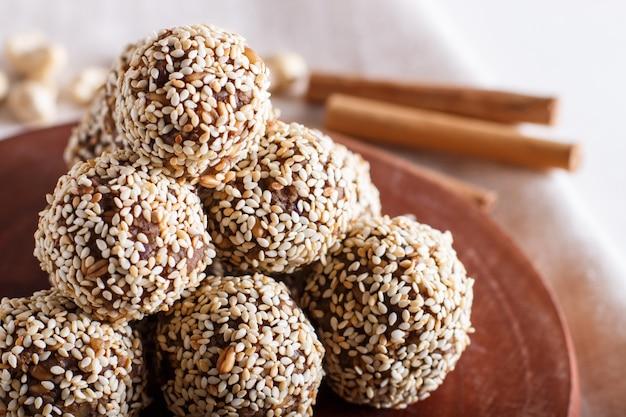 Boules d'énergie gâteaux aux amandes, sésame, noix de cajou, noix, dattes et blé germé, vue latérale, gros plan.