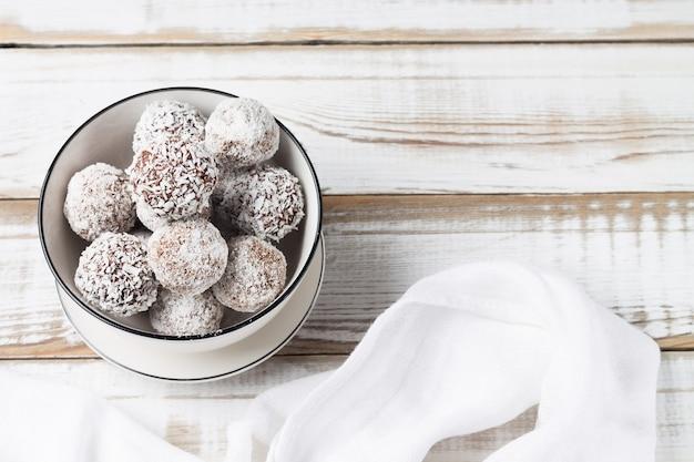 Boules d'énergie à la noix de coco dans une tasse blanche. copiez l'espace. la nourriture saine