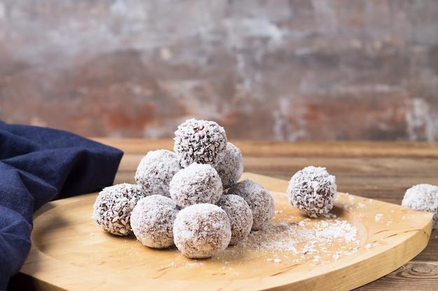 Boules d'énergie de noix de coco sur un plateau en bois, sur une table en bois.