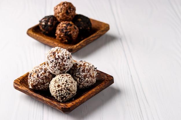 Boules d'énergie saine de noix, flocons d'avoine et fruits secs avec noix de coco, lin et graines de sésame sur des plaques de noix de coco en bois sur fond blanc, orientation horizontale, espace de copie
