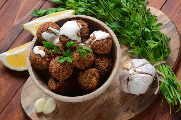 Boules de falafel au persil dans un bol en bois avec sauce tahini