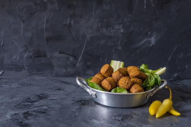 Boules de falafel servies en assiette avec green leafs sur fond noir en bois