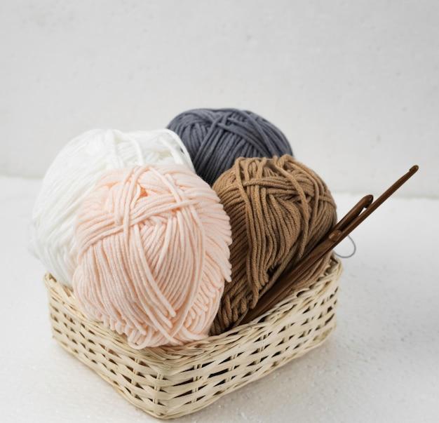 Boules de fil et crochets en bois dans un panier tressé