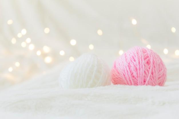 Des boules de fil à tricoter se trouvent sur un fond clair