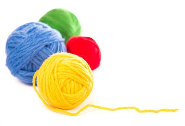 Boules de fils de laine bleus, rouges et jaunes sur fond blanc